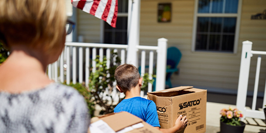 A mother and son carry moving boxes