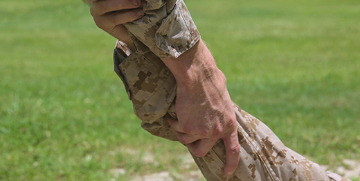 Service member grabbing other service member's hand in support